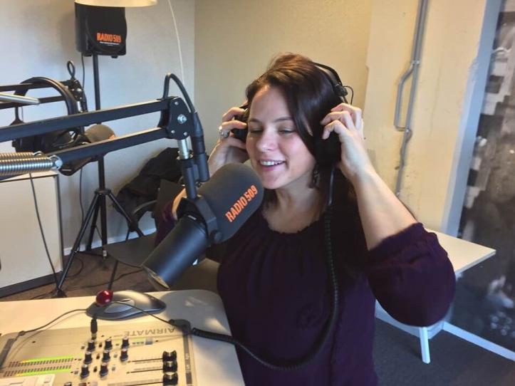 Annemiek in een radio uitzending, zittend met koptelefoon op haar hoofd
