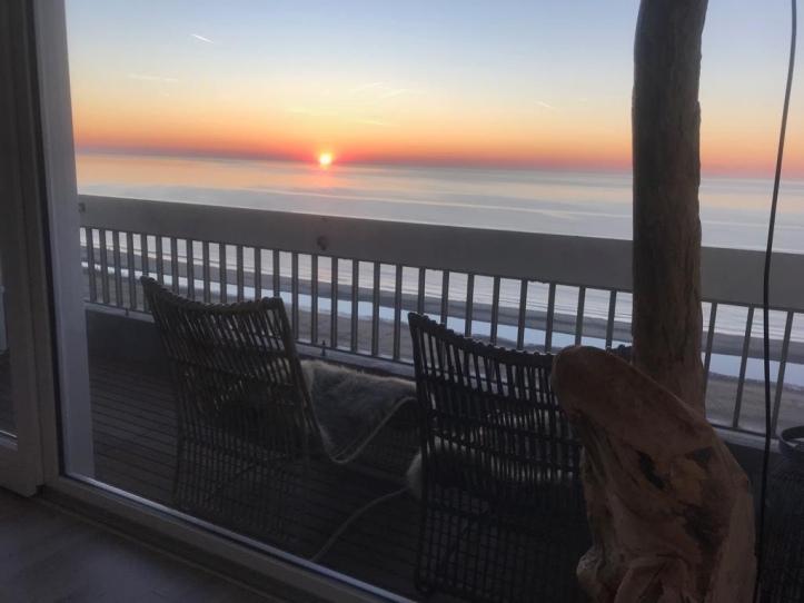 foto van stoelen op balkon zeezicht met ondergaande rode zon